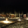 The camp area lights provide a warm glow against the cold snow.- The Rolling Huts