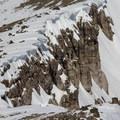 Skiers exploring a wind-scoured Castle Peak-Basin Peak ridgeline.- Castle Peak