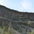 A domineering wall of columnar basalt rising above the Chimney Rock Trail.- Chimney Rock Trail