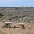 Bench overlooking the Crooked River Canyon with the Three Sisters, Broken Top, and Mount Bachelor in the distance.- Chimney Rock Trail