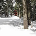 Departing from the parking lot on the cat track with the Mountaineers' winter cabin in view.- Grace and Summit Lakes