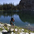 A backpacker passes one of many lakes in the Alpine Canyon cirques.- Alpine Creek Canyon