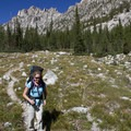 A hiker descends the trail down Alpine Canyon with Perfect Peak (10,269') towering behind.- Alpine Creek Canyon