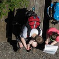 Some hikers looking at a map while resting below.- Heybrook Lookout