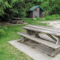 Privy and picnic tables at the trailhead.- Rock Trail