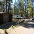Vault toilet facilities at Camp Sherman Campground.- Camp Sherman Campground