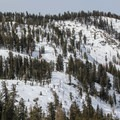 The return route pushes back over the The Hump saddle, retracing the route of the ascent.- Wolverton to Pear Lake Ski Hut