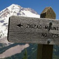 Zigzag Mountain Trail sign with Mount Hood in the background.- Burnt Lake + Zigzag Mountain