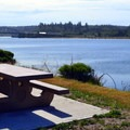 Picnic table next to the Coquille River in the day use area.- Bullards Beach State Park