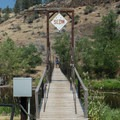 A swaying suspension bridge leads to the hot springs.- Ritter Hot Springs