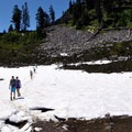 Crossing snowfields in Upper Morovitz Meadow.- Park Butte