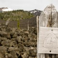 Pacific Crest Trail marker. Left to right in the distance: Belknap Crater (6,877'), Little Belknap Crater, Mount Washington (7,795').- Little Belknap Crater