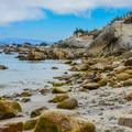 The beach turns into a rocky shoreline.- Lovers Point Beach