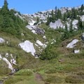 Lush, green meadows and pale gray boulders cover the ground above Minotaur Lake.- Minotaur Lake