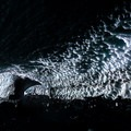 Light bounces around the ice caves. A small waterfall drips from a hole in a crevasse.- Big Four Ice Caves