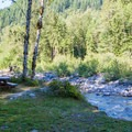 Picnic area by the river.- Miller River Group Campground