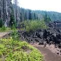 A user trail follows the lava's edge .- Hand Lake