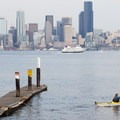 A kayaker launches from the Don Armeni Boat ramp on Alki Beach.  - Blake Island State Park Sea Kayaking