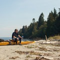 A kayaker takes a breather on the western side of Blake Island near the Cascadia Marine Trail campsites.- Blake Island State Park Sea Kayaking