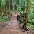 The well-maintained trail includes log stairs.- Deception Falls Interpretive Trail