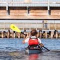 Kayaking under the Madison Street pier.- Port Townsend Sea Kayaking