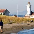 A couple walks along the beach toward the Point Wilson Lighthouse.- Port Townsend Sea Kayaking