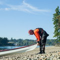 A kayaker pulls his boat onto the beach at Hope Island.- Hope Island State Park Sea Kayaking
