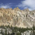 Towering red and green granite walls above the east shore of Hidden Lake.- South Fork of the Payette River, Hidden Lake and Cramer Divide