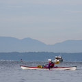A kayaker makes her way to Carkeek Park with the Olympic Mountains in the background.- Golden Gardens to Carkeek Park Sea Kayaking