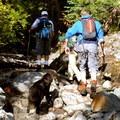 Hikers walk through a wet, rocky creekbed.- Railroad Grade Trail