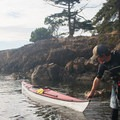 A kayaker pulls his boat up to a beach near the campsites on Jones Island.- Jones Island Sea Kayaking