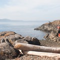A kayaker takes his boat down to the beach at Jones Island.- Jones Island Sea Kayaking