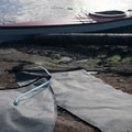 A camper dries out gear at Blind Island.- Blind Island Sea Kayaking