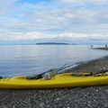 Kayak on Orcas Island's North Beach with Matia Island in the distance.- Orcas Island to Sucia Island Sea Kayaking
