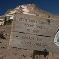 The PCT runs alongside Mount Hood through Paradise Park. A sign indicates the mileage to the trail's endpoints.- Mount Hood Wilderness