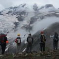 A hiking group looks up at Mount Rainier (14,411') on the way to Camp Muir.- Camp Muir Hike