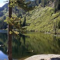 Enjoy Heather Lake while resting on flat rocks by the shore.- Heather Lake Trail