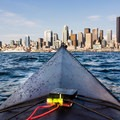 A large wave sends the bow of the the kayak above the horizion.- Elliott Bay Sea Kayaking