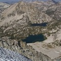 Looking down onto Plummer Lake (foreground) and Everly Lake from the summit of Plummer Peak. The prominent red dike on the east ridge (right) of Mount Everly can be traced for nearly 15 miles through the Sawtooths.- South Fork of the Payette River, Everly Lake, Plummer Lake + Everly Divide