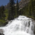 Rushing water pours over a granite bedrock slab en route to Redfish Lake.- Redfish Inlet Hikes