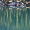 Pine trees reflected in the third Saddleback Lake.- Saddleback Lakes