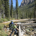 A climber approaches the log crossing of Redfish Lake Creek.  This is a dangerous crossing during spring runoff.- Saddleback Lakes