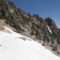 Enjoying a snowfield above Goat Lake. The town of Stanley can be seen in the valley far below.- Goat Lake via the Alpine Way Trail