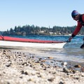 A kayaker pulls his boat into the water off the shore of Cutts Island.- Cutts Island Sea Kayaking