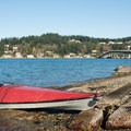 A kayak sits at the boat launch near the Fox Island Bridge.- Fox Island Sea Kayaking