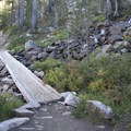 Several truncheon bridges cross seeps and creeks en route to Imogene Lake.- Imogene Lake + Divide