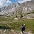 A hiker climbs though one of several alpine meadows on the Broad Canyon Trail.- Broad Canyon: Betty, Goat + Baptie Lakes and the Surprise Valley Divide