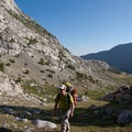 A backpacker looks for a campsite at the end of the grassy medows.- Fall Creek - Left Fork Canyon