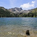 Lower Sardine Lake, backed by Sierra Buttes (8,587'), is a 0.3-mile walk away by trail.- Sardine Lake Campground