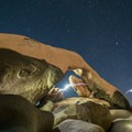 Exploring an arch at night along the Arches Rock Nature Trail in Joshua Tree National Park.- Arch Rock Nature Trail